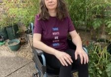 Image of Philippa Fleming sitting in her wheelchair in her back garden.
